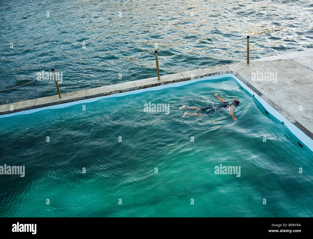A swimmer floating and snorkeling in a seaside pool. - Stock Image