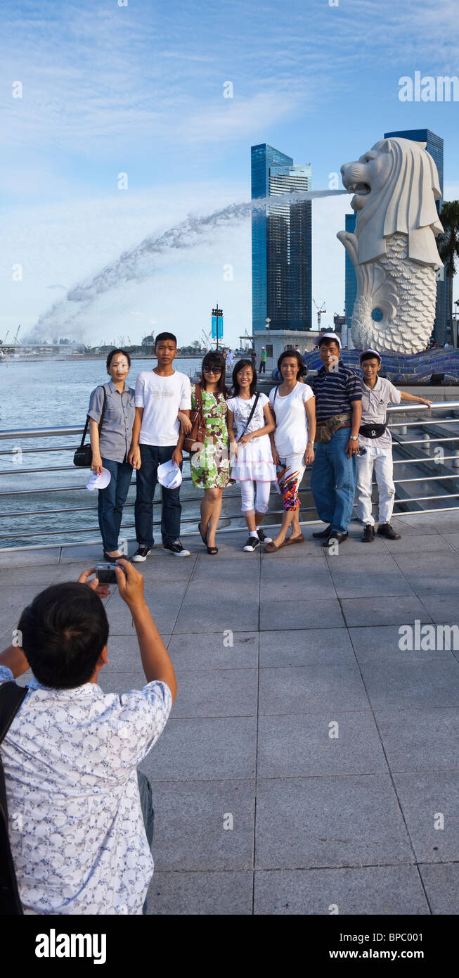 tourists taking photographs in front of the merlion, the symbol of Singapore - Stock Image