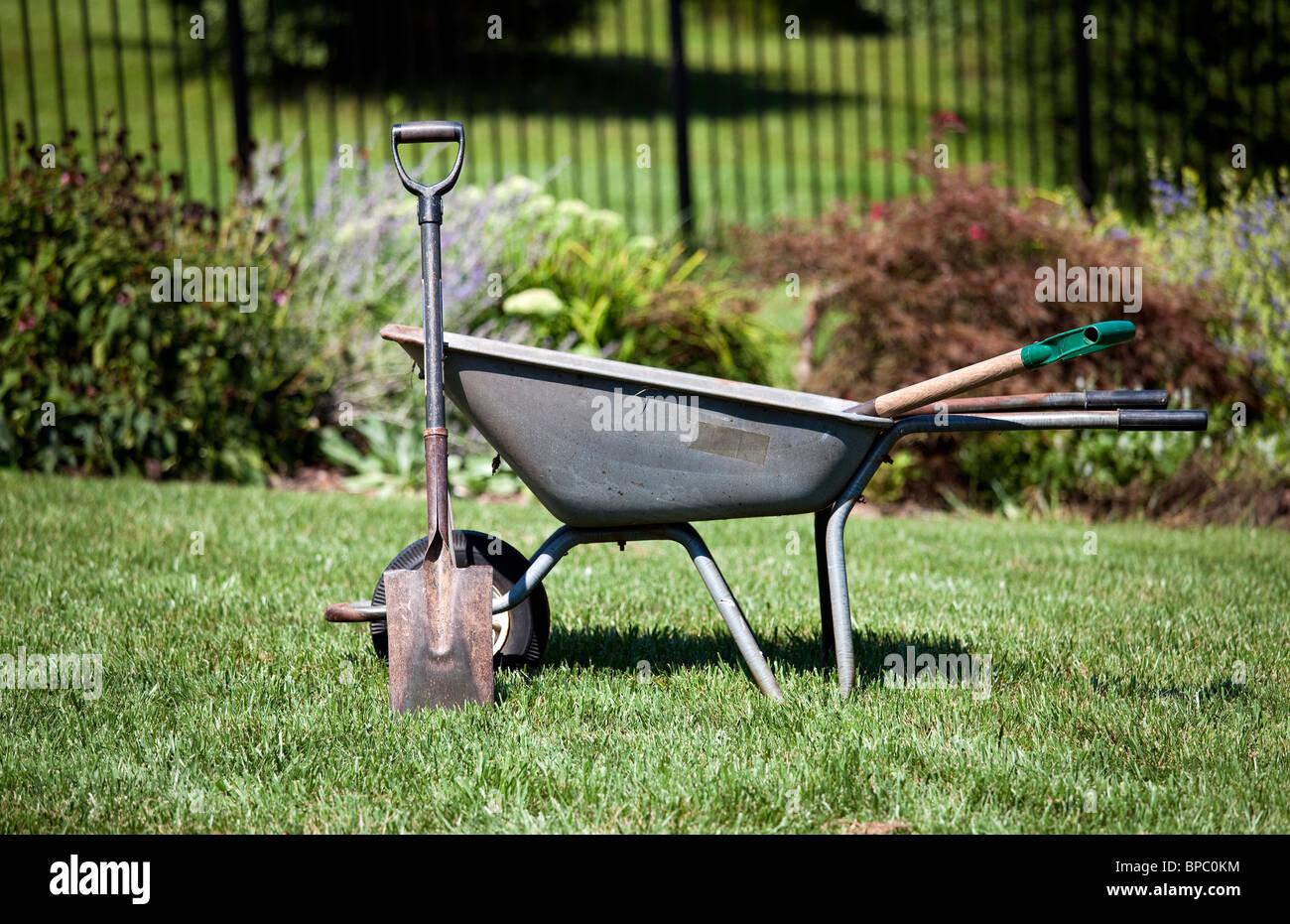 Garden tools - Spade resting against a wheelbarrow in a garden - Stock Image