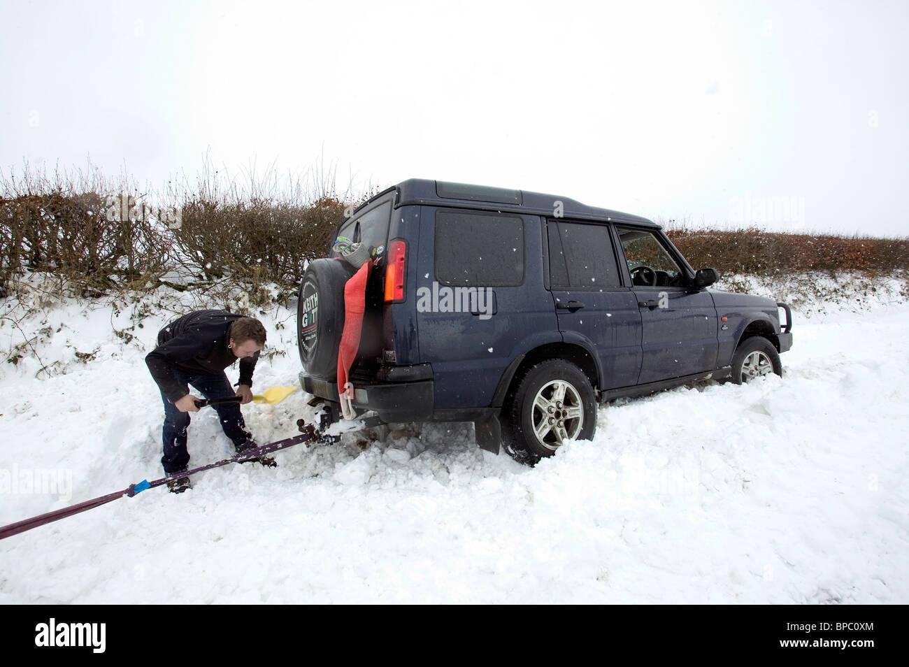 Man digging out snowed in four-wheel drive, Dartmoor, Devon - Stock Image