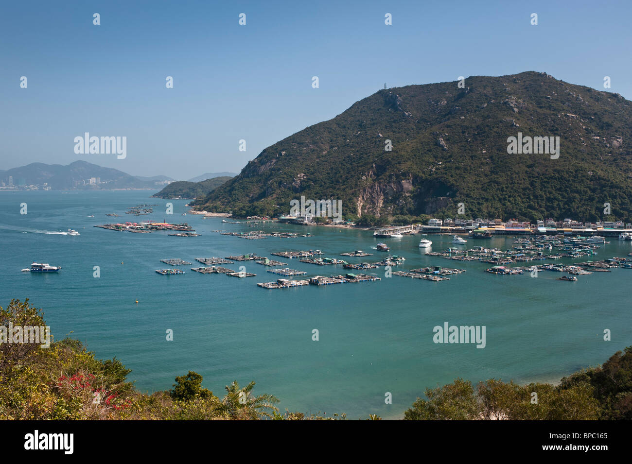 Picnic Bay on Lamma Island with Sok Kwu Wan village. A lot of fish farming going on in the sheltered bay. - Stock Image