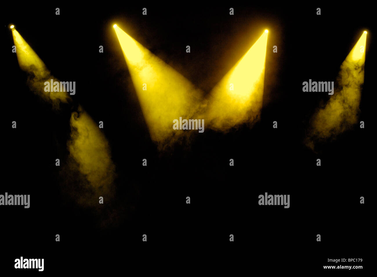 Yellow stage spotlights in smoke over black background - Stock Image
