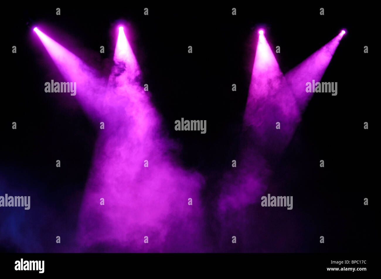 Purple stage spotlights in smoke over black background - Stock Image