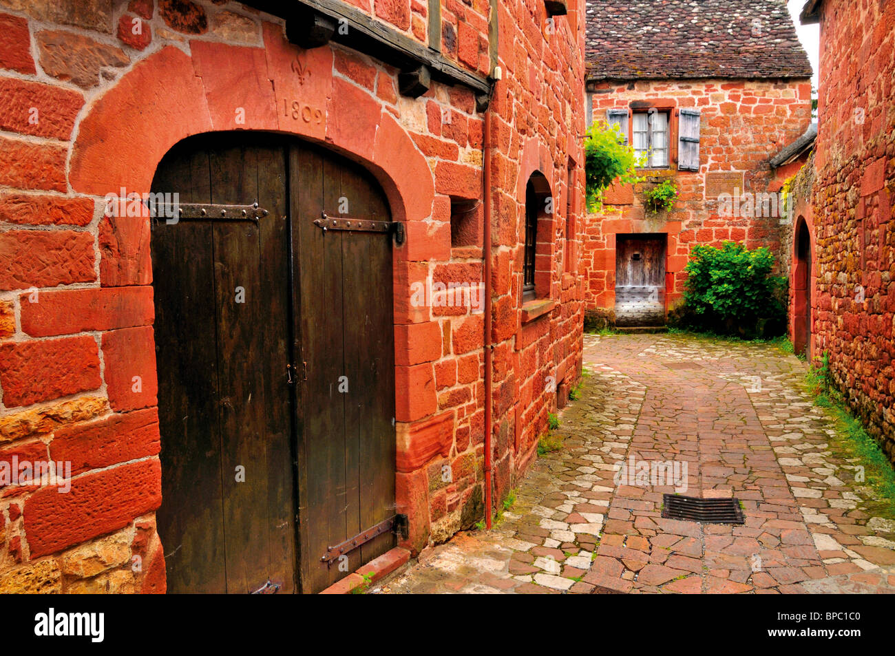France: Alley and red sandstone houses in medieval village Collonges-la-Rouge - Stock Image