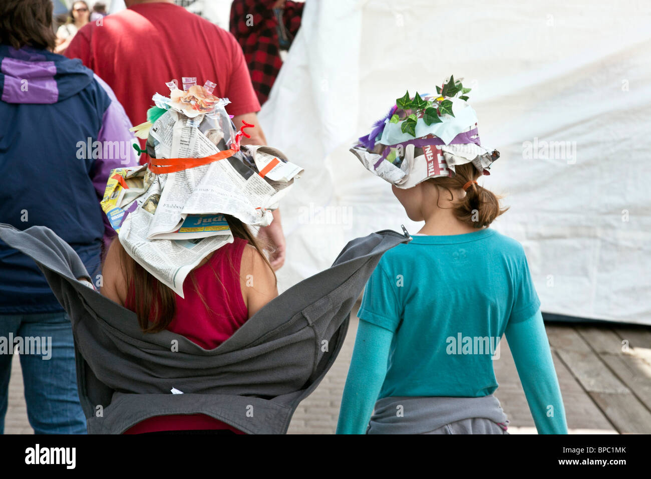 two little girlfriends wearing fanciful decorated paper hats of their own invention at Everett waterfront art festival - Stock Image