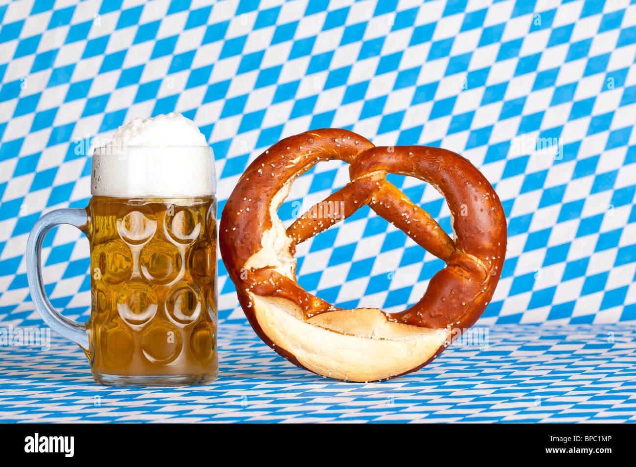 oktoberfest beer stein with pretzel and bavarian flag in background