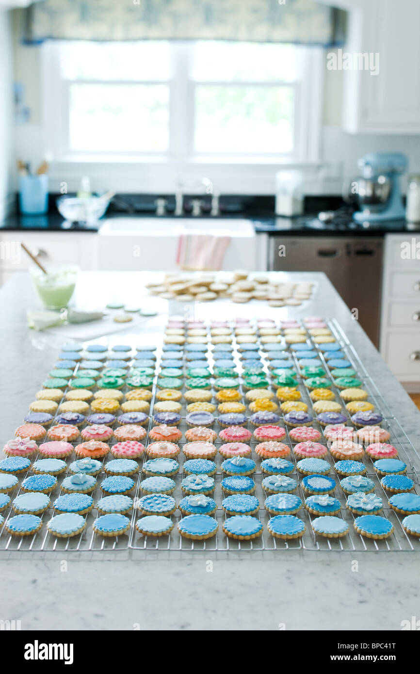 Beautiful multicolored frosted cookies in kitchen - Stock Image