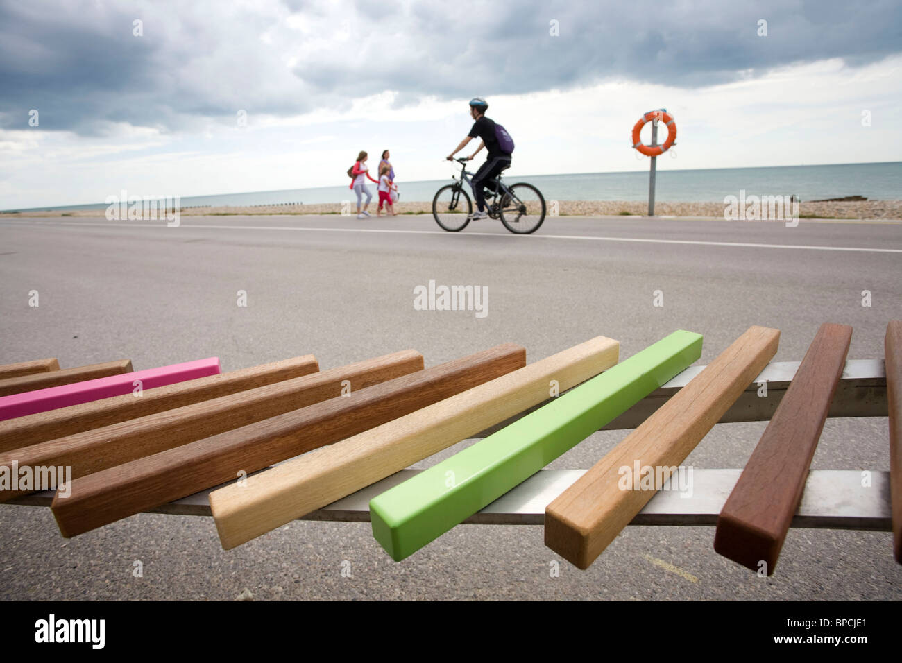 People on Littlehampton seafront  go past a section of the Long Bench. Picture by James Boardman. - Stock Image