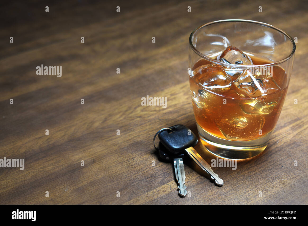 Glass of whiskey and car keys on wooden table. Stock Photo