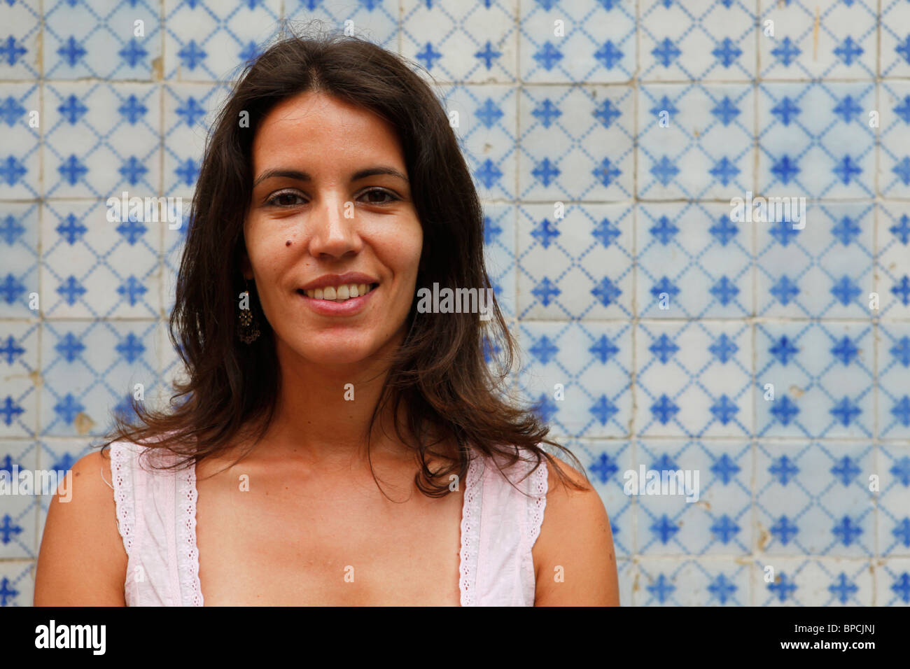 A Portuguese woman stands in front of blue and white Azulejo tiles which are typical of buildings throughout the - Stock Image