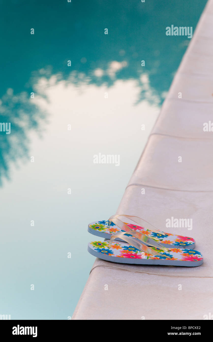 flip-flop near swimming-pool in morning sun - Stock Image