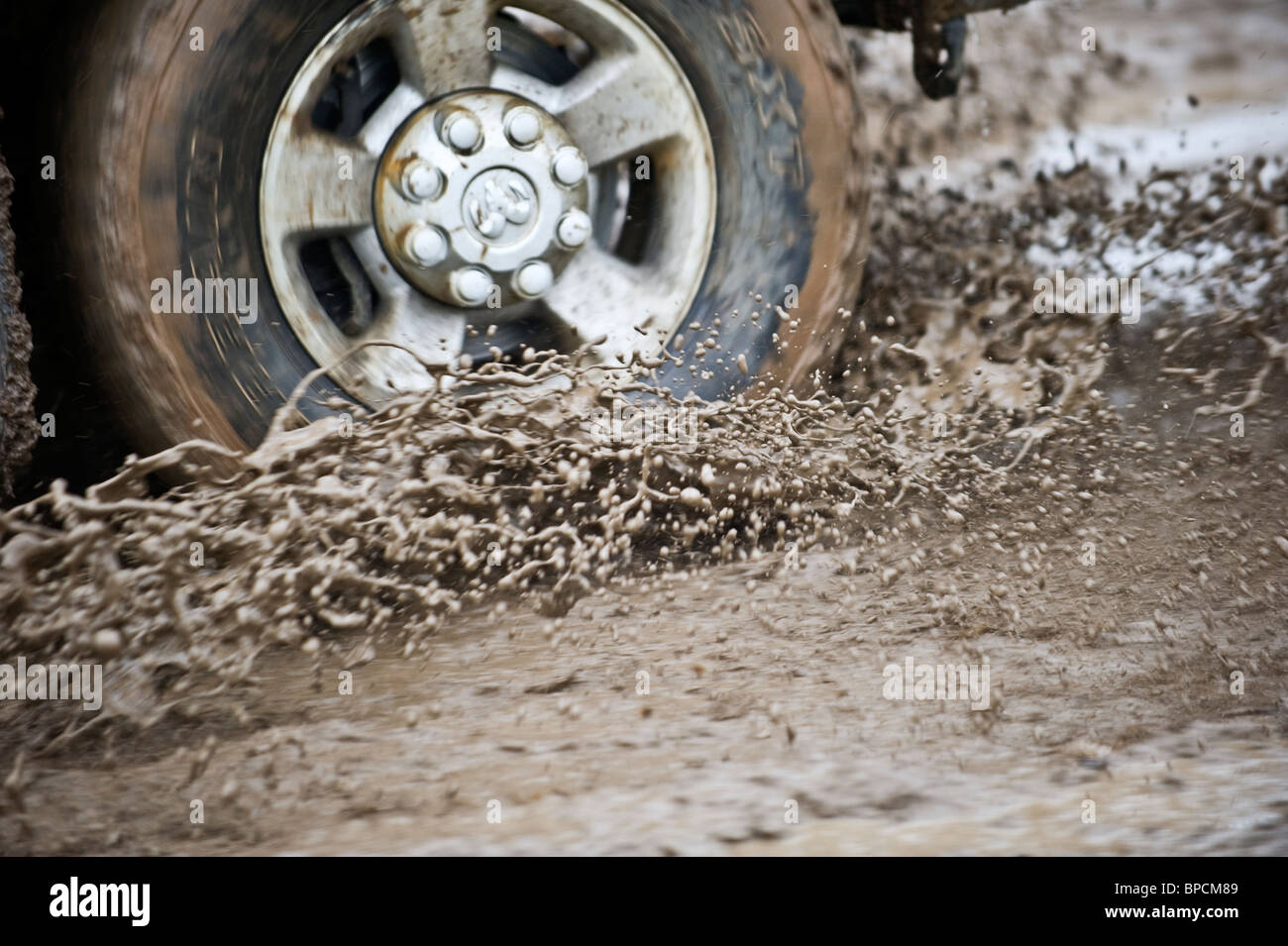 An image of a truck wheel and tire spinning through a mud hole. - Stock Image