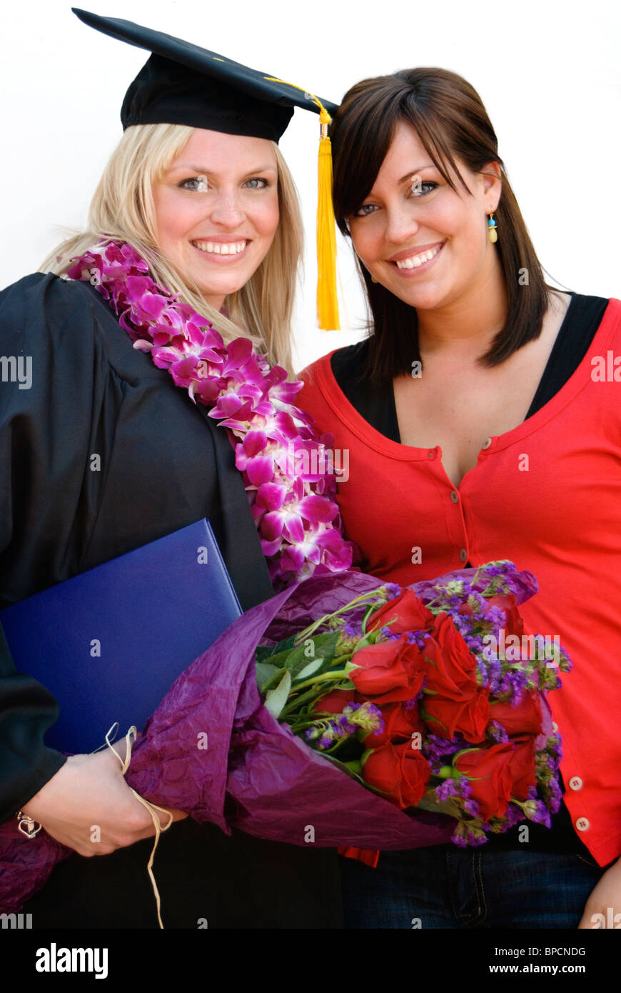 A smiling graduate in cap and gown wearing lei stands with supportive friend. Stock Photo