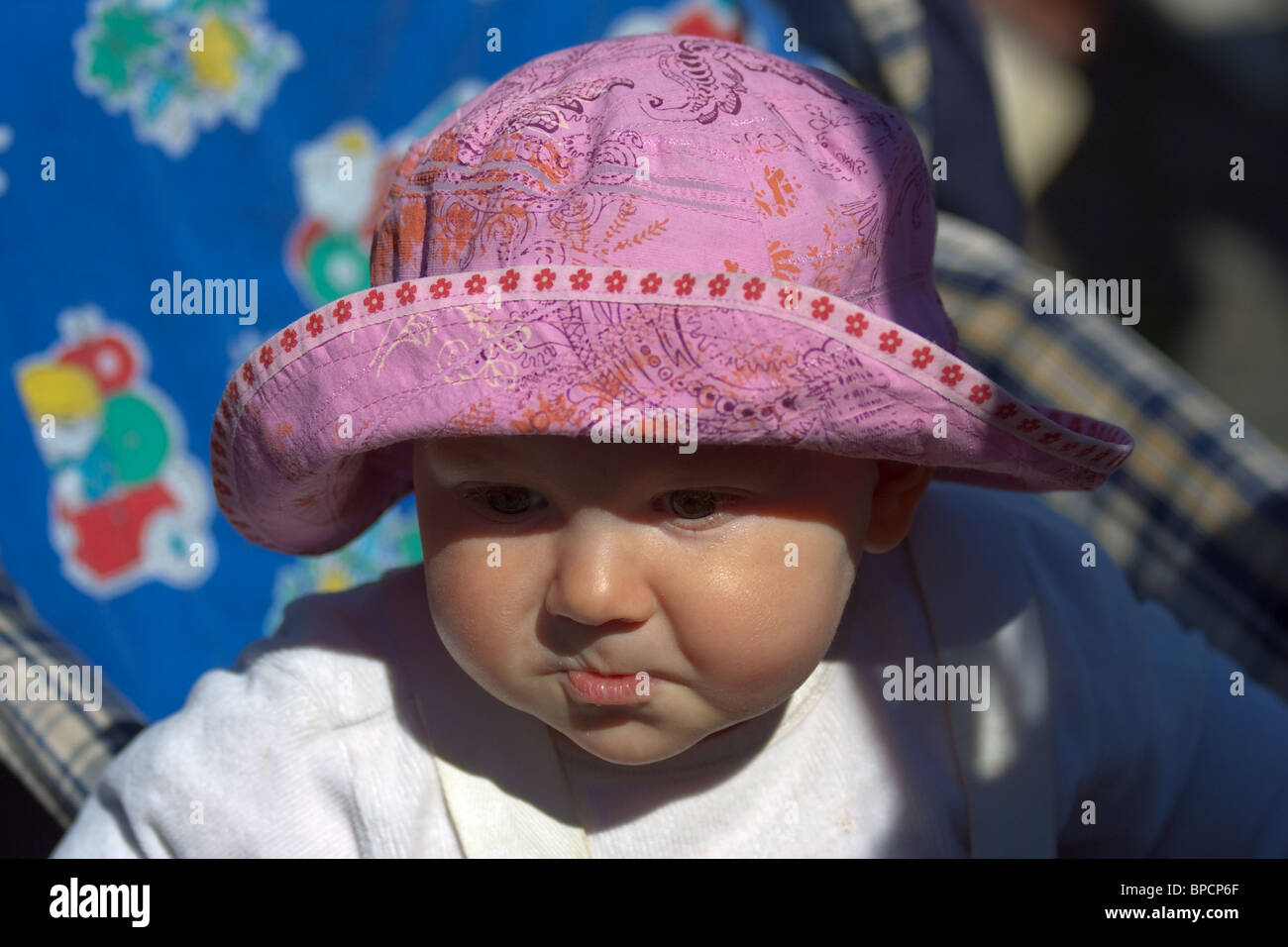 close-up of adorable baby with round cheeks sailor hat and disgruntled expression. Horizontal - Stock Image