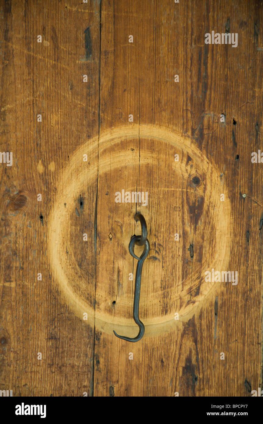 Metal hook on worn wooden door - Stock Image