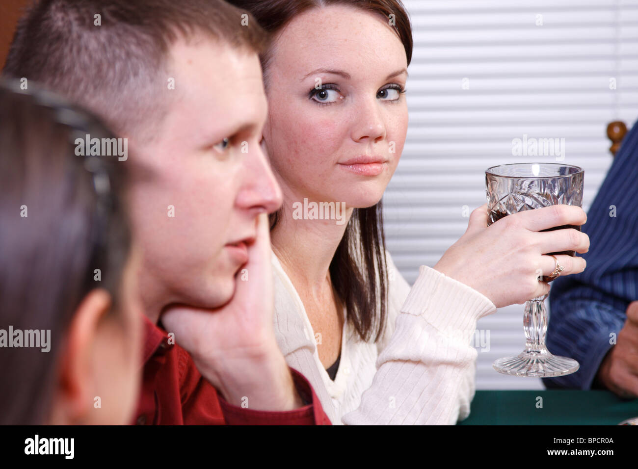Woman staring unhappily at man during family dinner - Stock Image