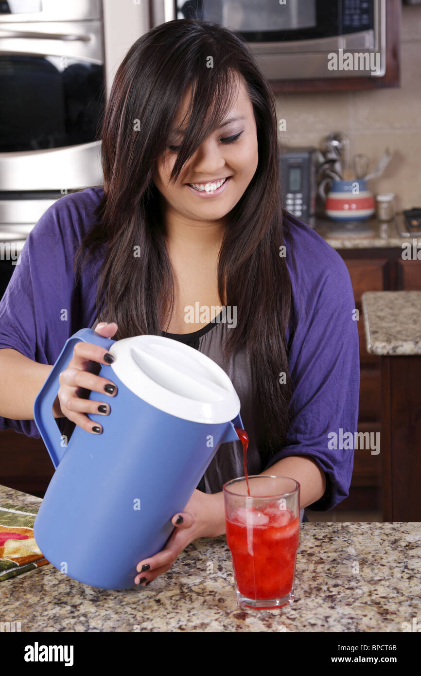 Teen pouring a glass of kool-aid Stock Photo