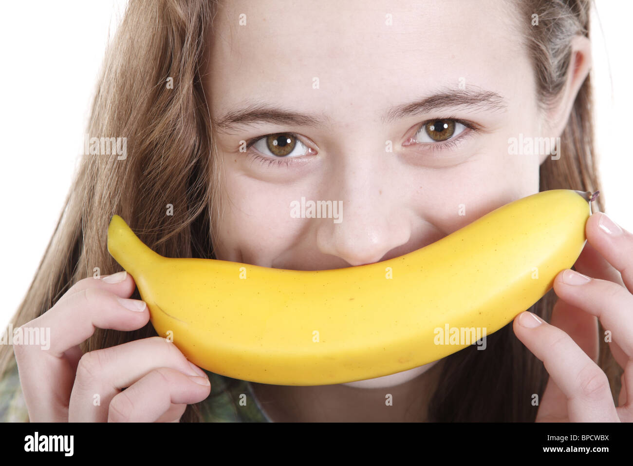 Teen girl holding a banana like a mustache - Stock Image