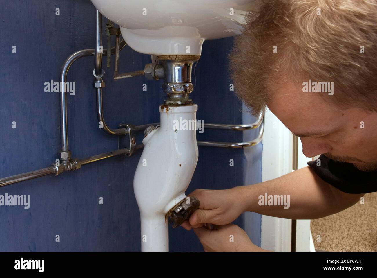 40 year old man trying to fix a stop in the washbasin pipe which is full of dirt and hair. - Stock Image