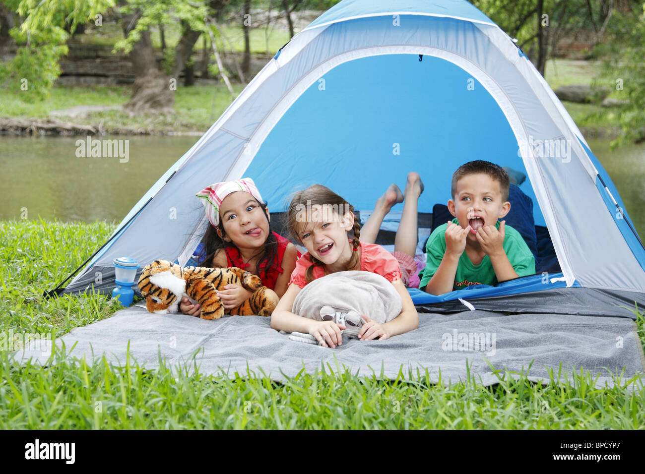 Kids in a tent acting goofy - Stock Image