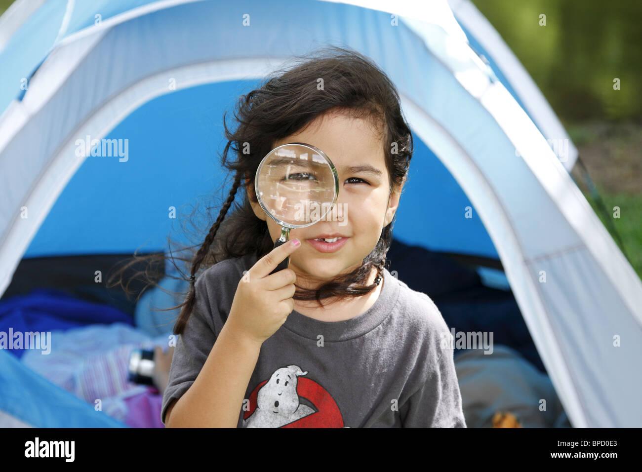 Girl looking at camera through magnifying glass - Stock Image