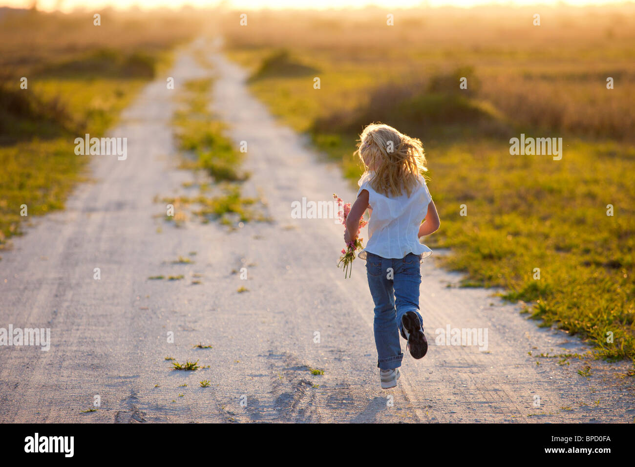 Rear view of young girl running on dirt road holding flowers - Stock Image