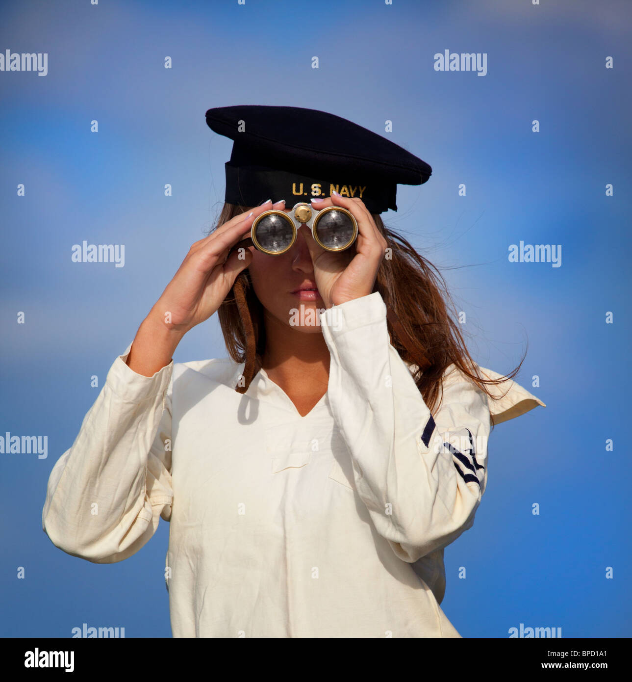 Young woman in the Navy looking through binoculars - Stock Image