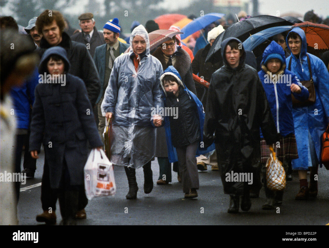 Crowds struggle through heavy rain after attending mass celebrated by Pope John Paul II in Knock, Ireland - Stock Image