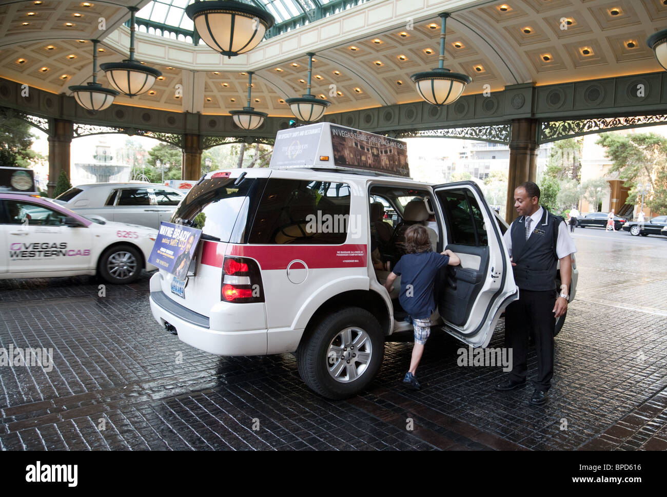 Bellboy helping people into a taxi, The Bellagio Hotel, Las Vegas Nevada USA - Stock Image