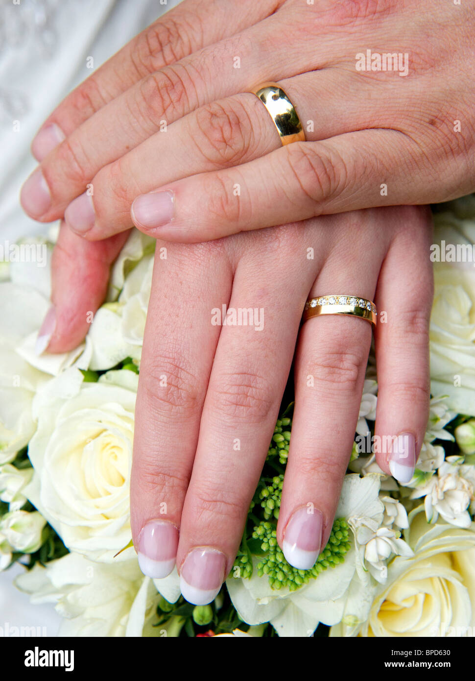 Man and womans hands held over bouquet of flowers and showing ...