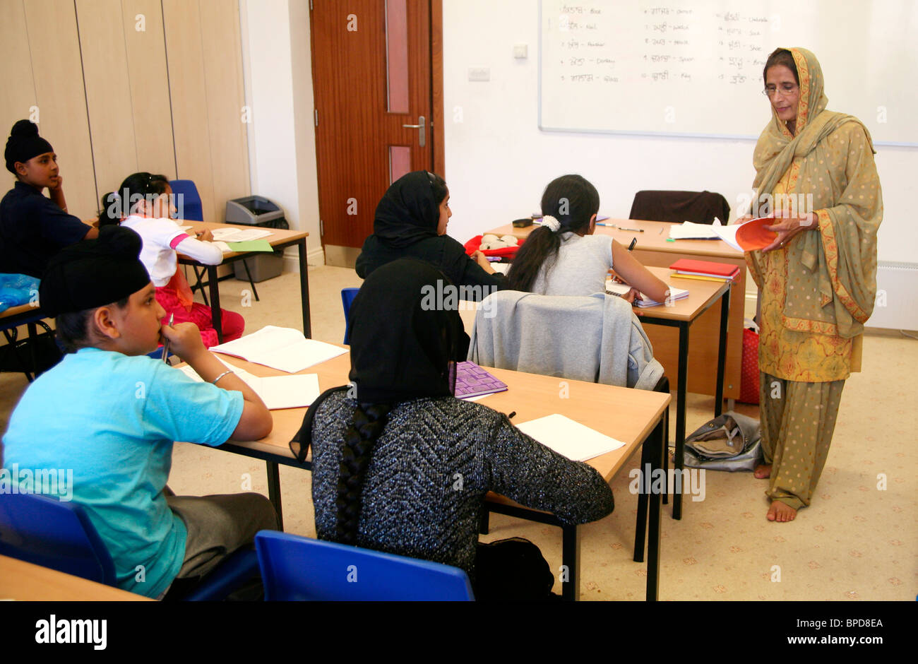 A female teacher taking a Punjabi lesson in Hounslow gurdwara, England - Stock Image