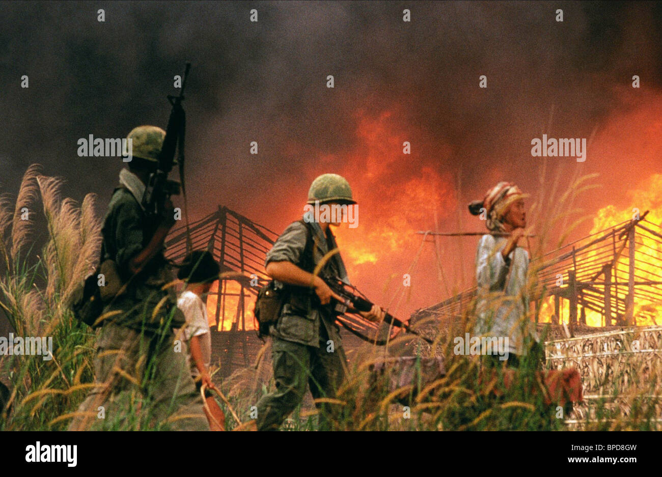 US SOLDIERS PASS BURNING HUTS CASUALTIES OF WAR (1989) - Stock Image