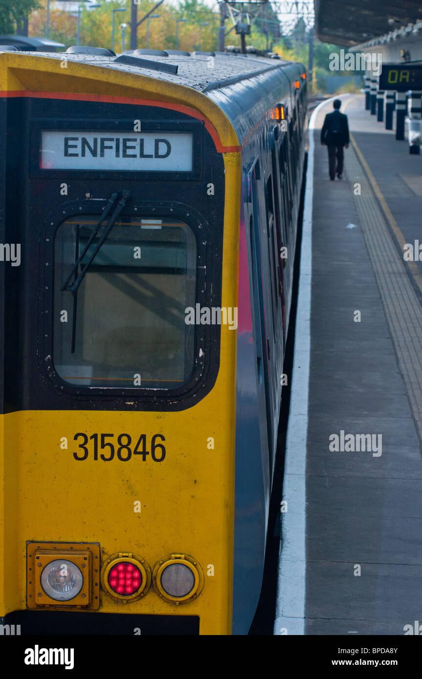 Suburban railway station and train, London, UK - Stock Image