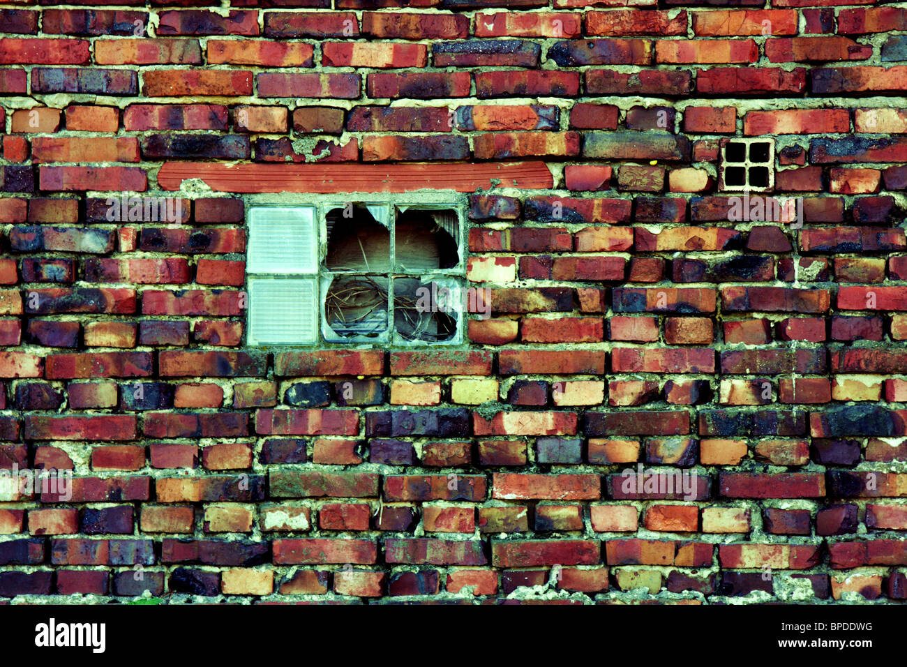 Broken window in red brick wall - Stock Image