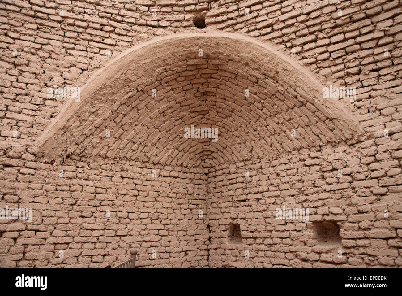 A mud brick wall and arch in the ruins of the ancient city of Jiaohe in the Takla Makan desert in Xinjiang, North - Stock Image