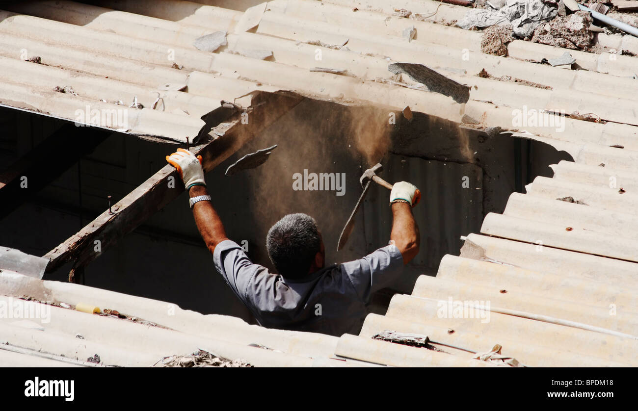 Spanish man removing old asbestos roof with hammer. No breathing mask or protective clothing amid clouds of dust - Stock Image