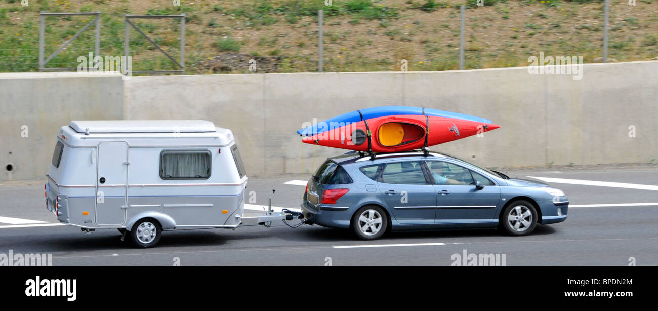 Car With Canoes On Roof Rack Towing A Small Caravan On The M25 Stock