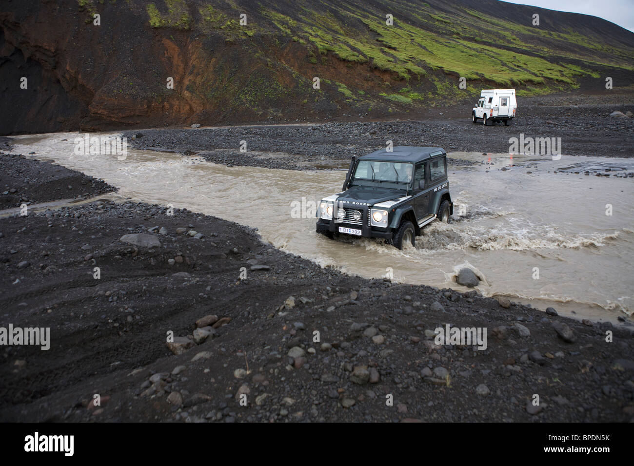 2 Land Rovers fording a river in the interior Highlands of Iceland. Defender 90 and a Defender 130 with a camper - Stock Image