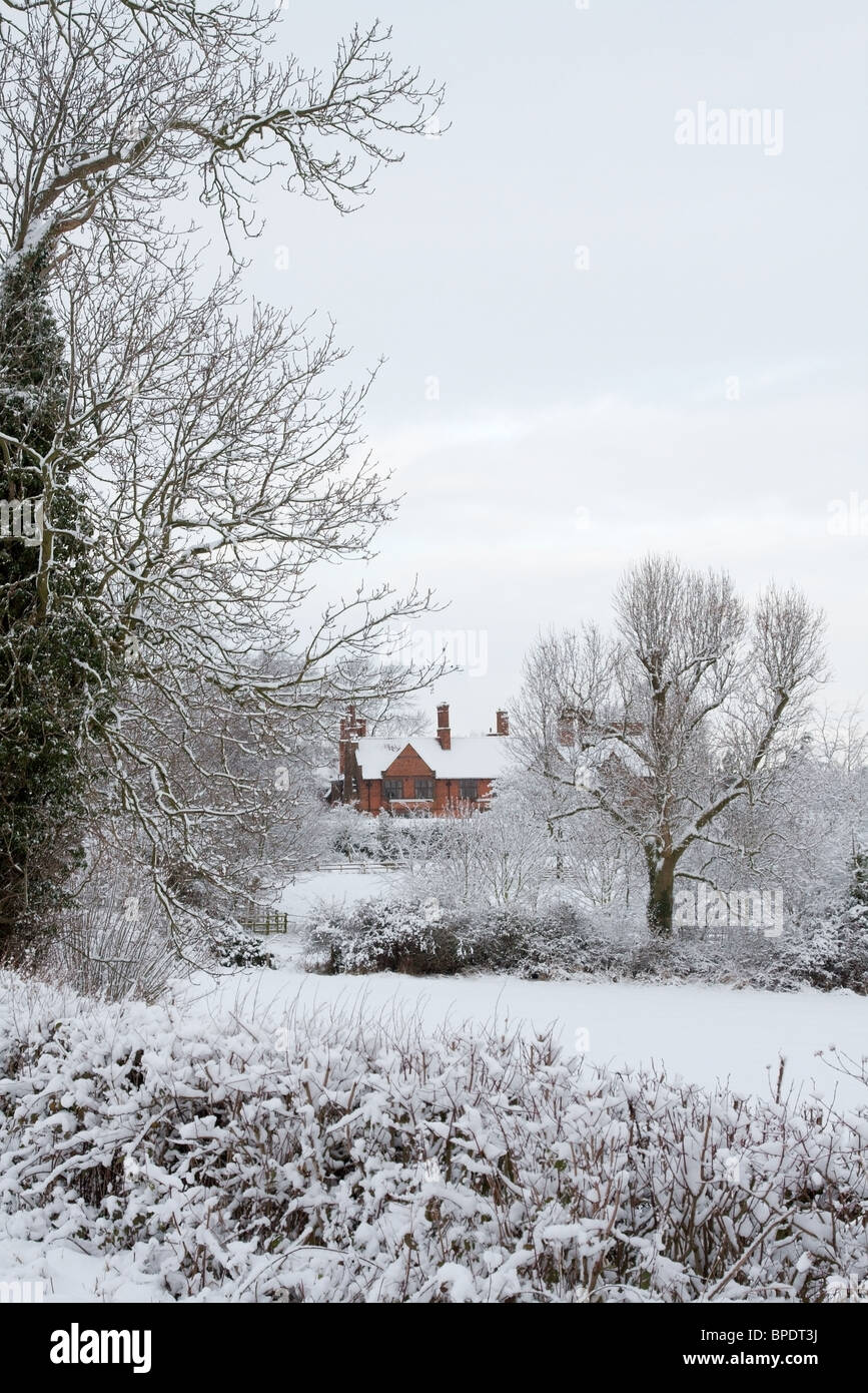 A large country house glimpsed through the trees under a fall of heavy snow - Stock Image