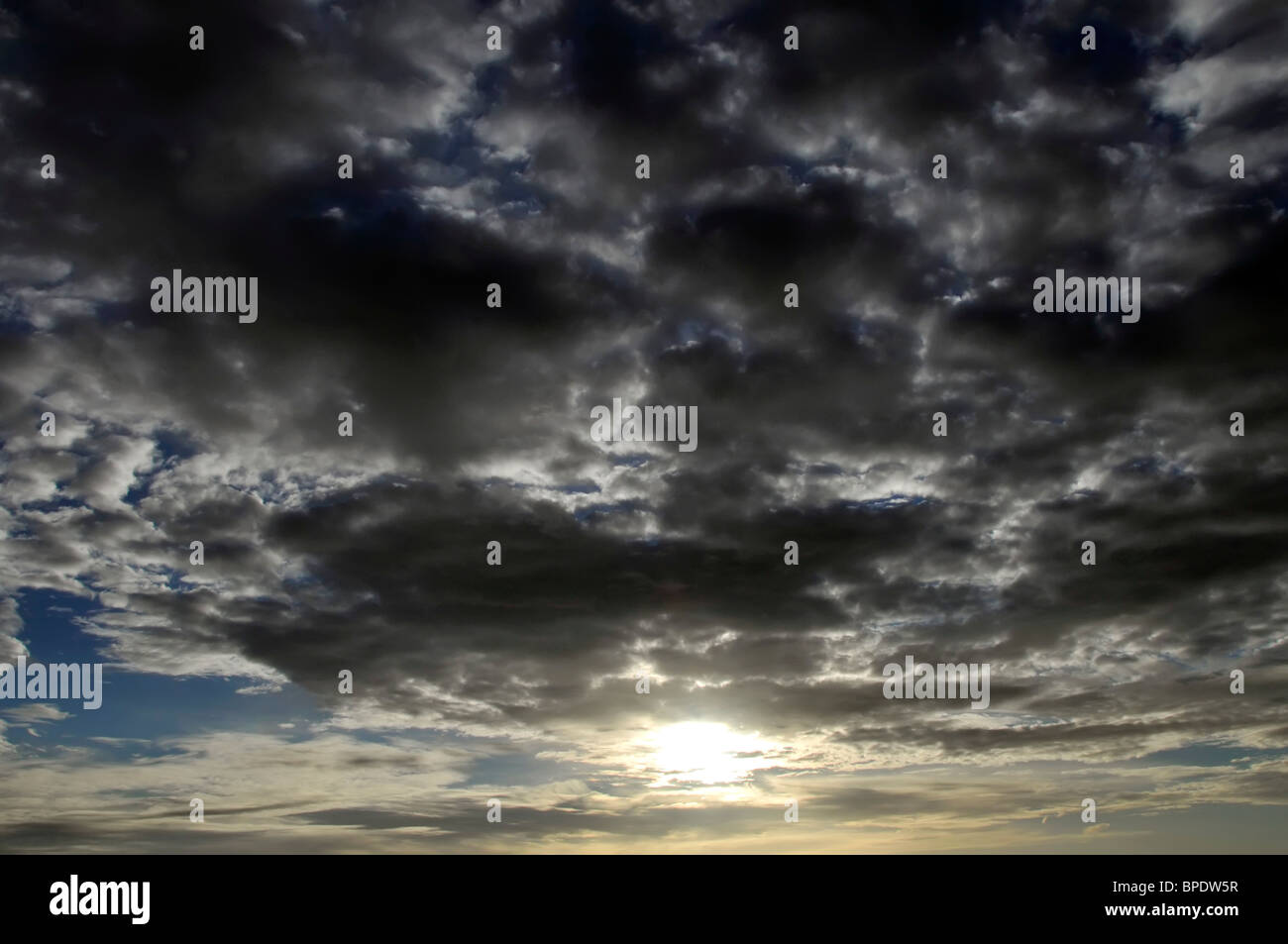 Dark black shower clouds just before sunset - Stock Image