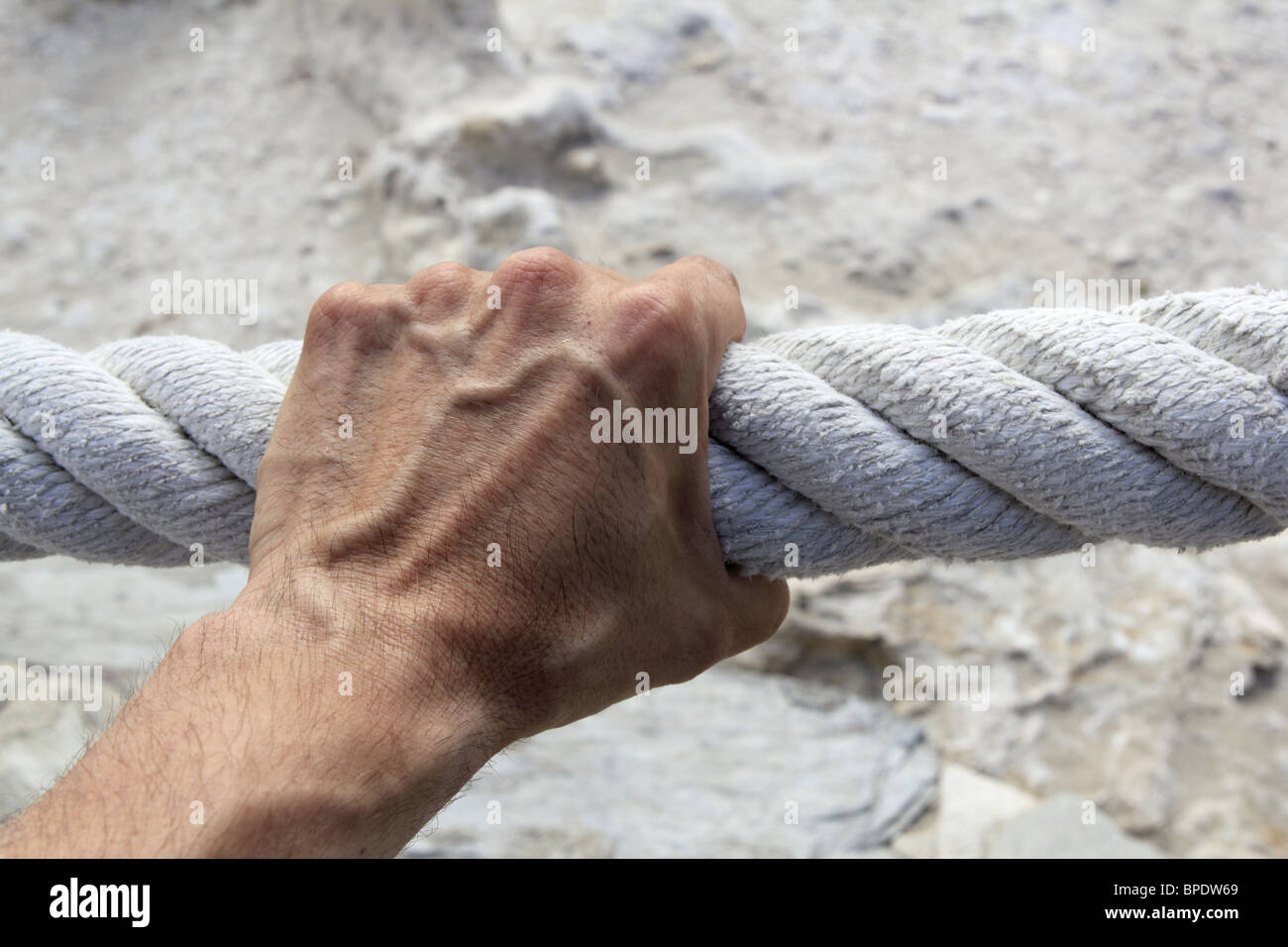 man hand grab grip holding strong big aged marine huge rope - Stock Image