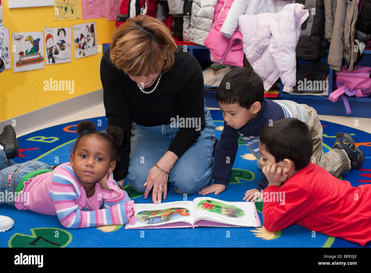 Preschool Teacher Reading A Book To Some Of Her 4 Year Old Students On The Floor