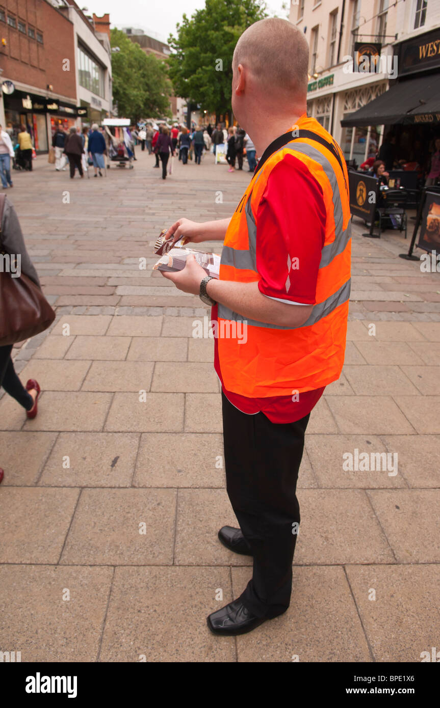 A McDonald's worker gives out leaflets in Norwich , Norfolk , England , Great Britain , Uk - Stock Image