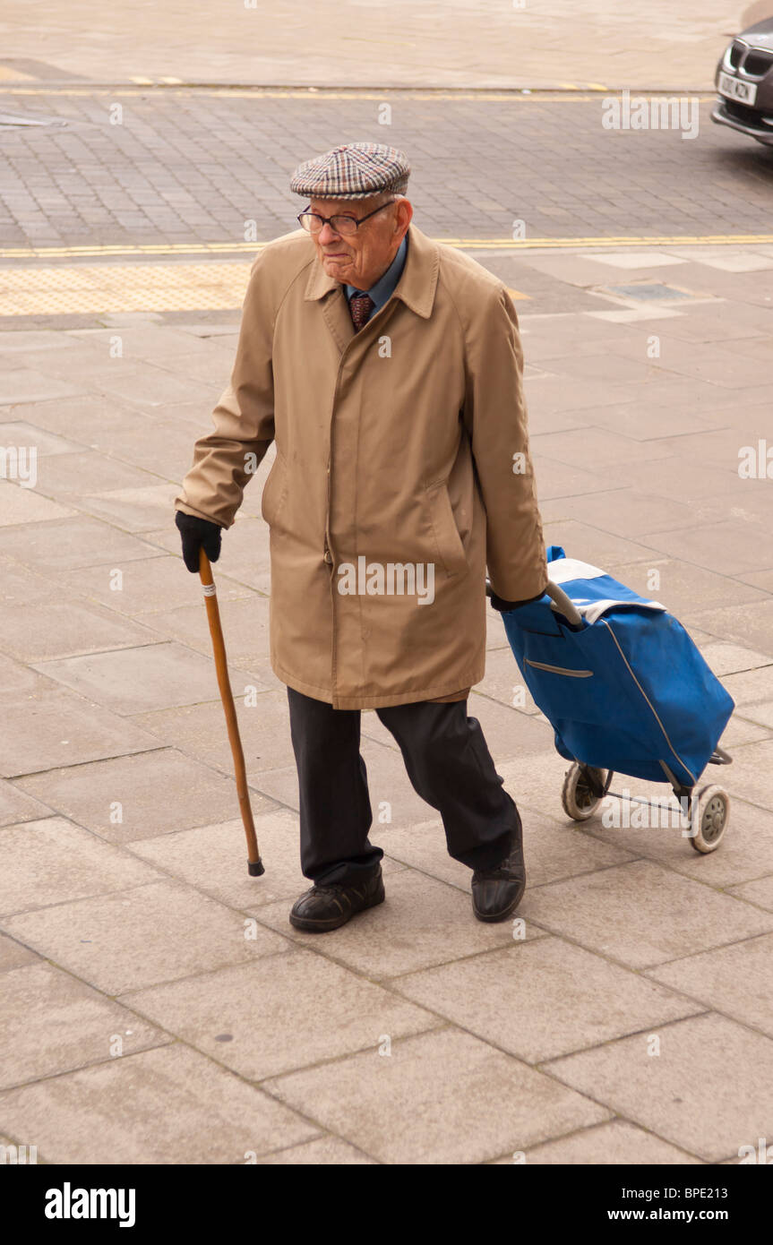 An elderly man with a shopping trolley and walking stick in the uk - Stock Image
