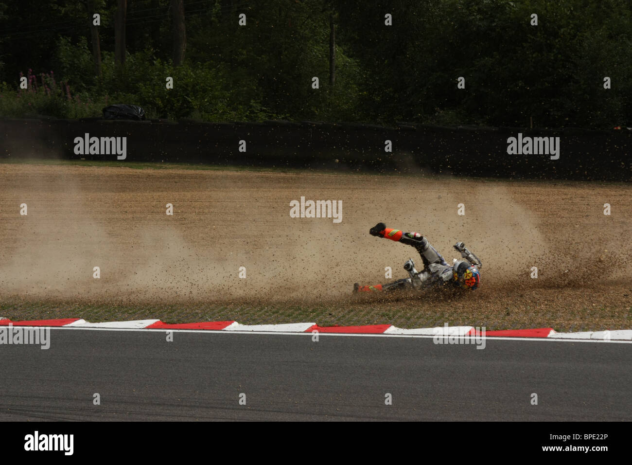 Rider slides through gravel after crashing out of the BSB at Brands Hatch - Stock Image