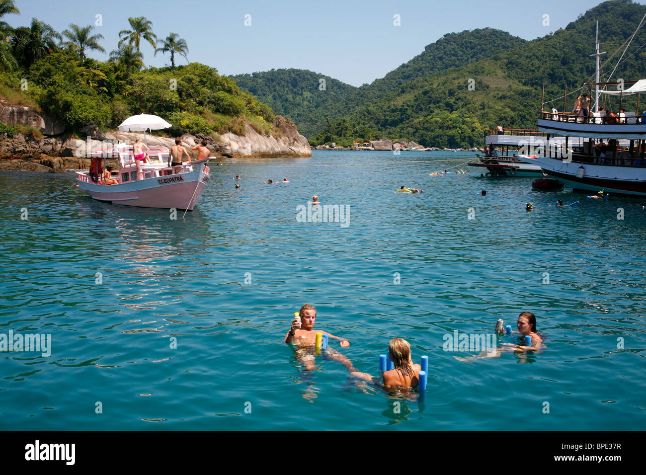 Tourist on a chartered fishing boat cruising between the different beaches and islands around Parati, Rio de Janeiro - Stock Image