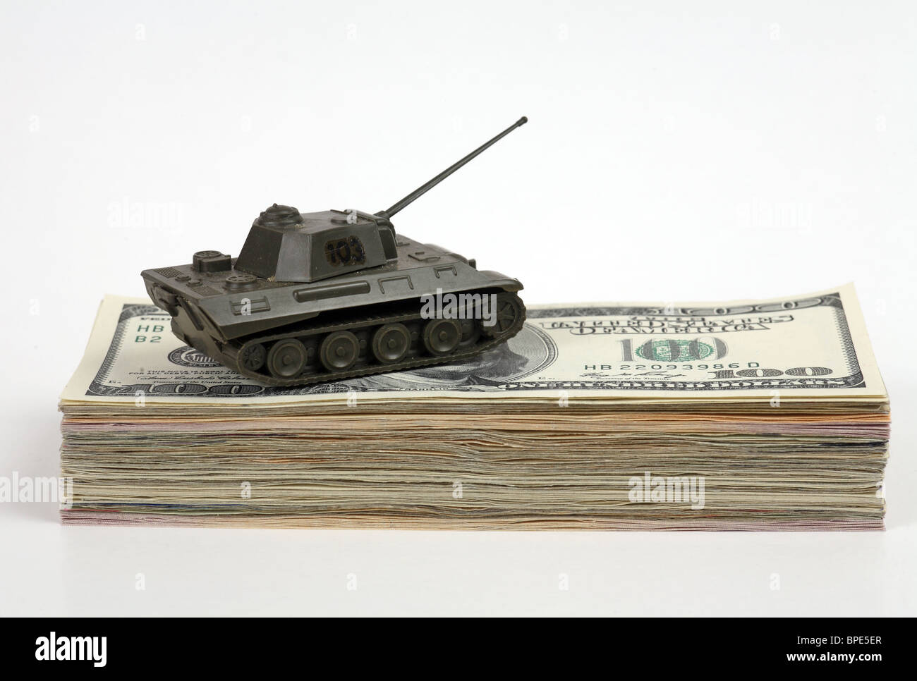A model tank on a wad of 100-dollar notes - Stock Image