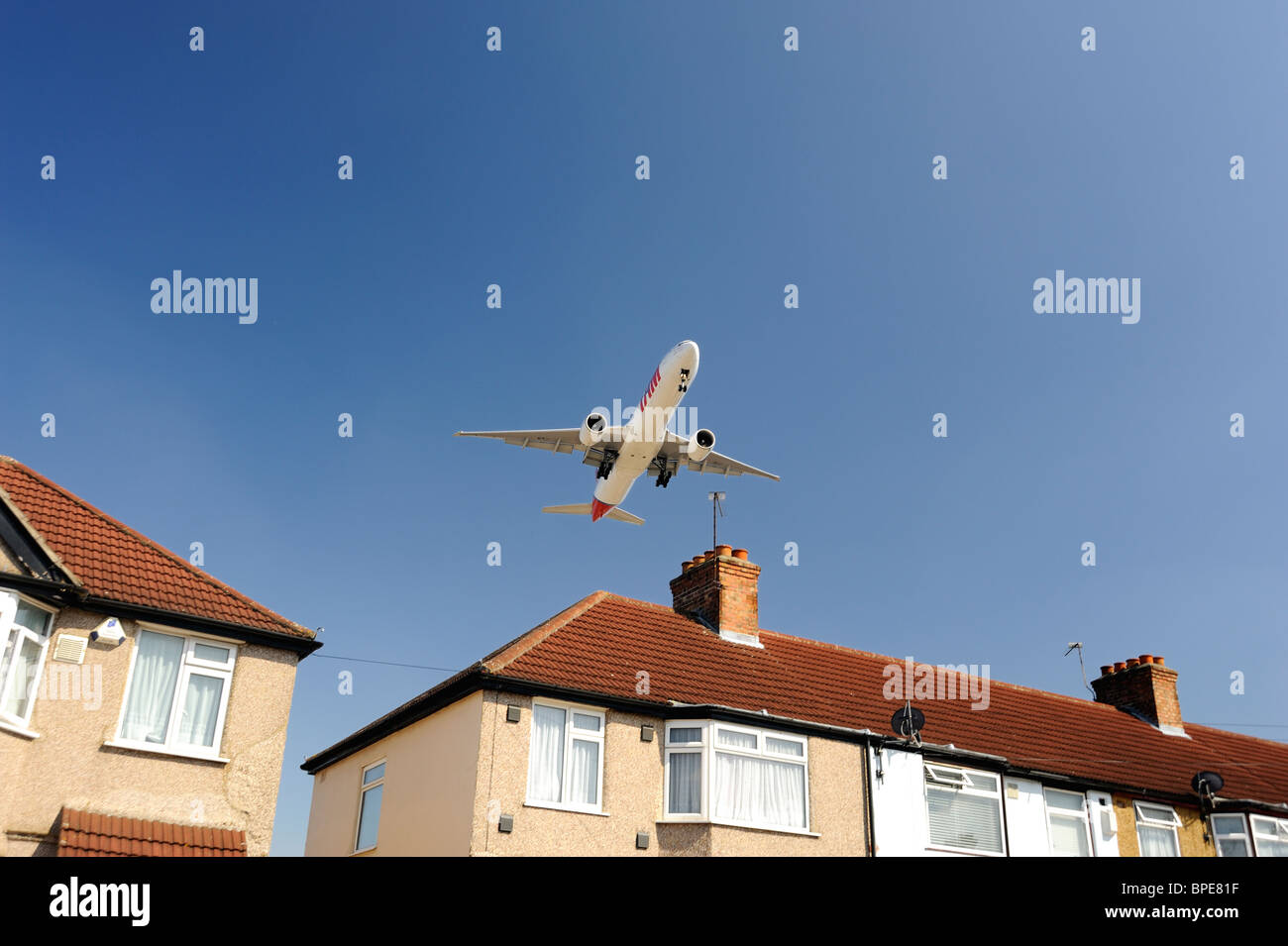 Airplane flying low over house prior to landing - Stock Image