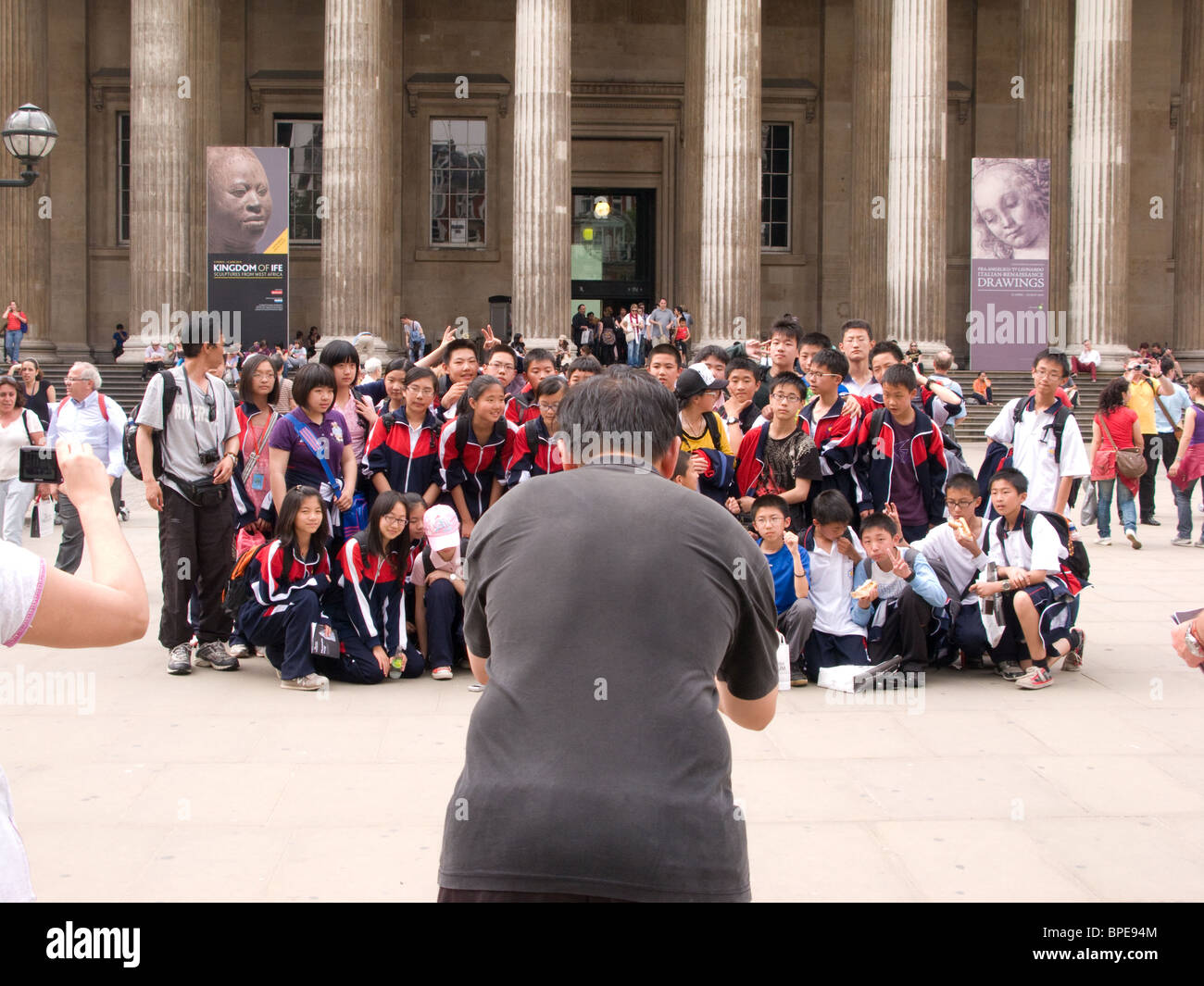 A teacher takes a photograph of foreign school children on a school trip to the British Museum - Stock Image