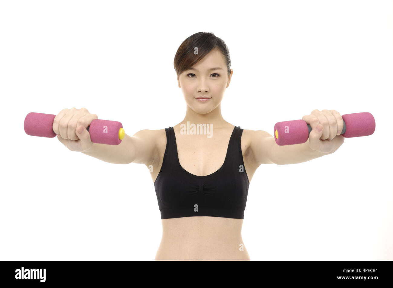 Woman lifting dumbbell indoors , smiling, portrait - Stock Image
